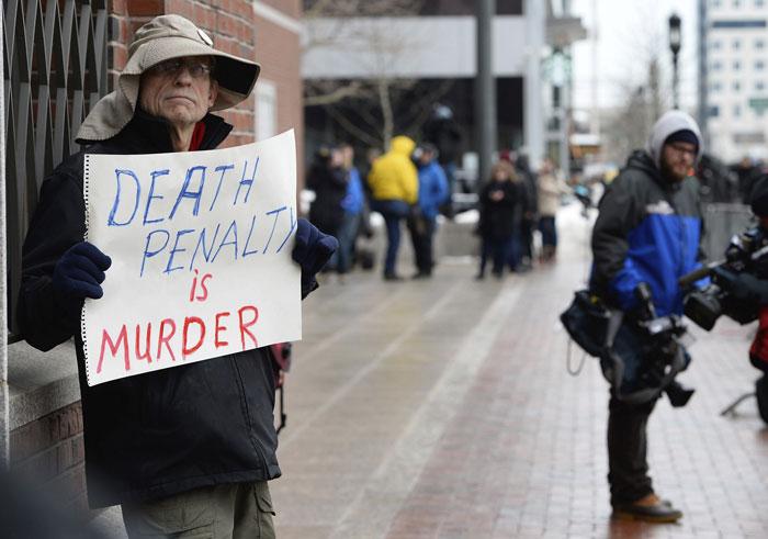"""Un ciudadano sostiene un cartel en el que se lee: """"La pena de muerte es asesinato"""" frente a la corte federal Joseph Moakley, en Boston, Massachusetts, Estados Unidos. EFE"""