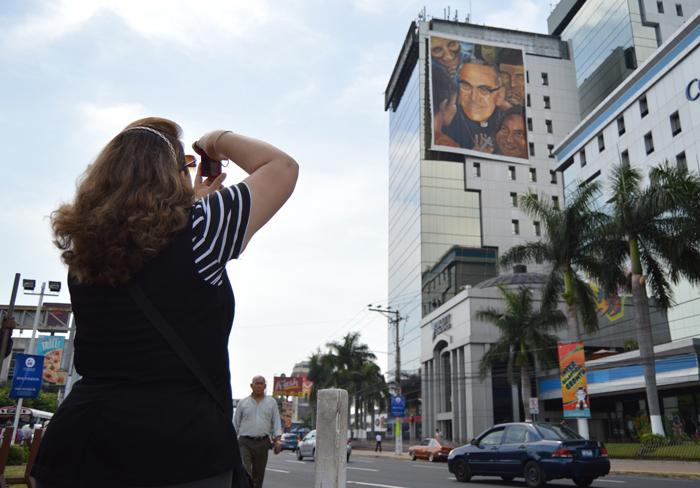 Turista toma una foto de un póster gigante de Romero colgado en la plaza Salvador del Mundo/.W .U.