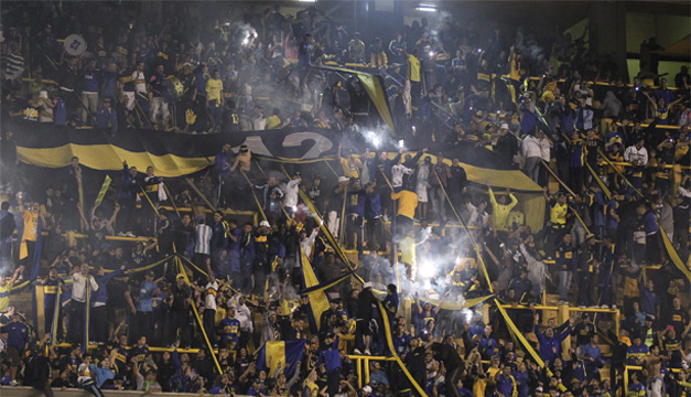 Seguidores del Boca Juniors reaccionan luego de que lanzaran gas pimienta desde la tribuna. EFE