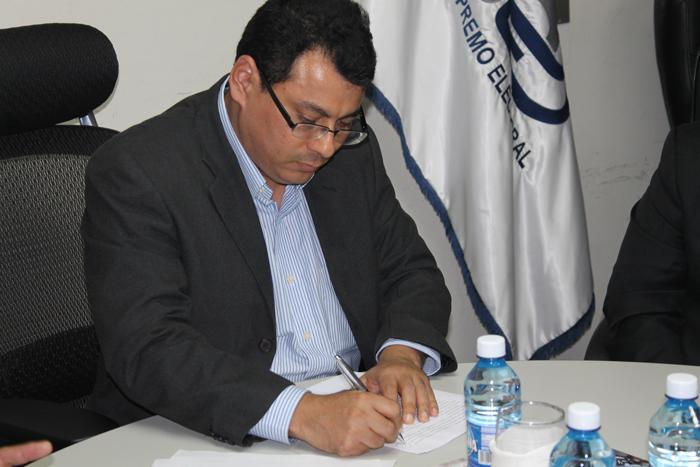 El presidente del TSE, Julio Olivo, firma el informe. /tse