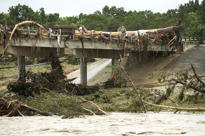 Policías inspeccionan un puente dañado por las inundaciones en Wimberley, estado de Texas. /XINHUA