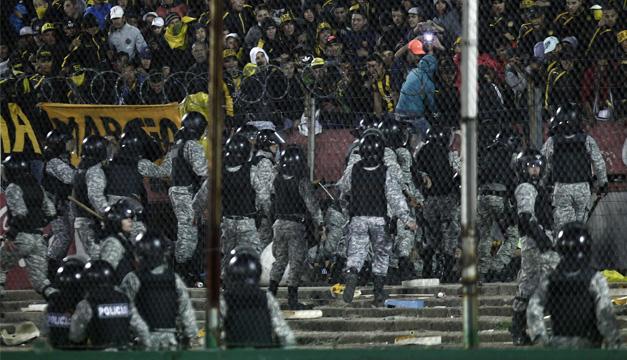Policías se enfrentan a aficionados de Peñarol hoy, domingo 14 de junio de 2015, durante el partido por la final del torneo Clausura 2015 del fútbol uruguayo, en el estadio Centenario de Montevideo (Uruguay).  EFE