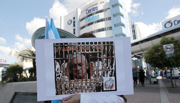 Una manifestante muestra un cartel con un fotomontaje donde se ve al presidente guatemalteco, Otto Pérez Molina, tras unas rejas. Foto/EFE.