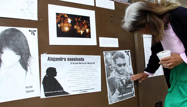Una mujer coloca una veladora a la entrada del edificio donde fueron asesinadas cuatro mujeres y un fotoperiodista. Foto/EFE