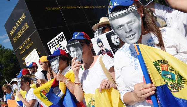 Con carteles y máscaras de presos políticos en Venezuela, venezolanos protestan pacíficamente. Foto: EFE.