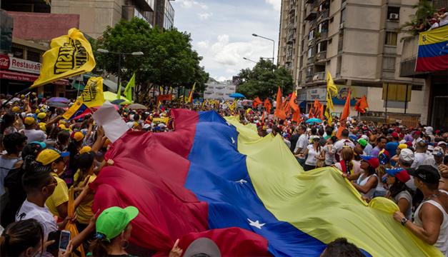 Un grupo de personas ondean una bandera venezolana. Foto/ACAN-EFE