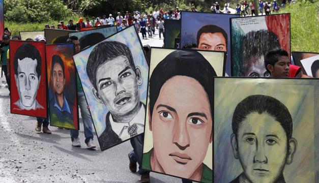 Normalistas de la escuela rural de Ayotzinapa sostienen retratos de los 43 estudiantes desaparecidos durante una caminata. Foto/EFE
