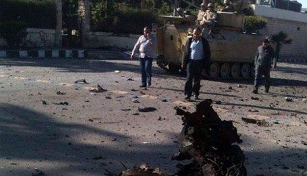 Varios restos esparcidos cerca de un vehículo militar blindado y personal de seguridad en el lugar donde se produjo un atentado suicida en Al Arish. EFE