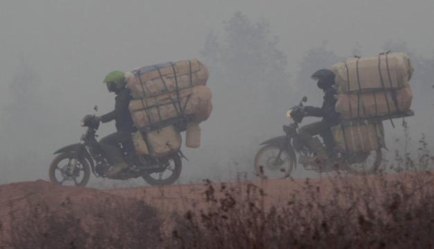 Dos campesinos trasladan fardos entre el humo de los incendios en los campos. EFE