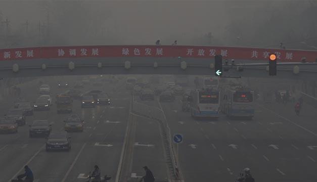 Coches circulan por una de las principales avenidas de Pekín en medio de una fuerte niebla causada por la contaminación. EFE