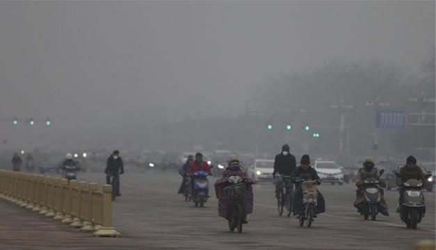 Motoristas usan mascarillas para protegerse de la contaminación en Pekín. EFE