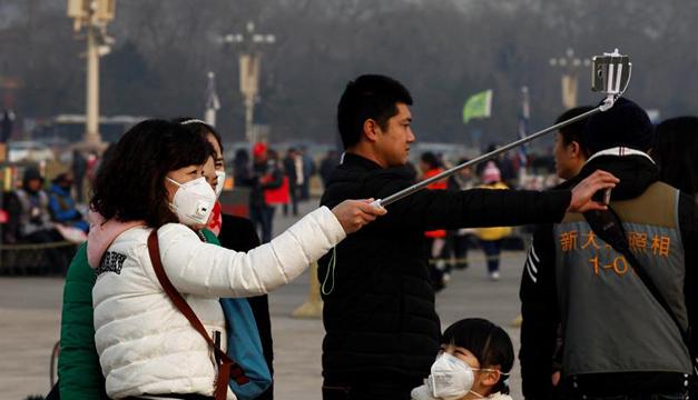 Turistas se hacen un selfi con las mascarillas en la plaza Tiananmen en Pekín. Foto: EFE
