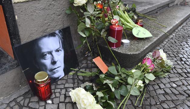 Fans depositan flores y velas junto a una foto el cantante británico David Bowie en un altar improvisado frente a su antigua residencia . EFE