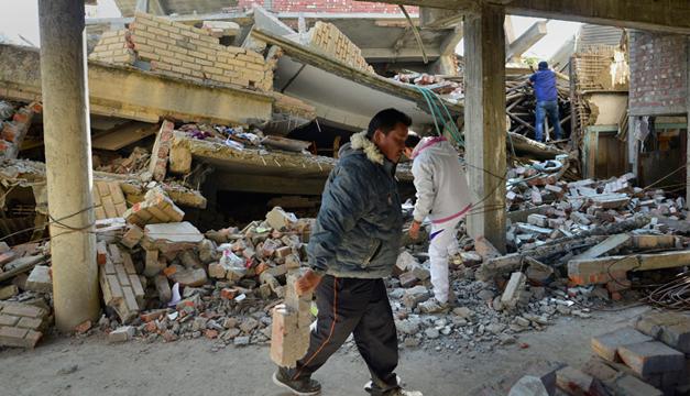 Varias personas inspeccionan las casas derruidas tras el terremoto. EFE