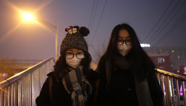 Dos jóvenes caminan en Pekín, protegidas con mascarillas por la contaminación. EFE