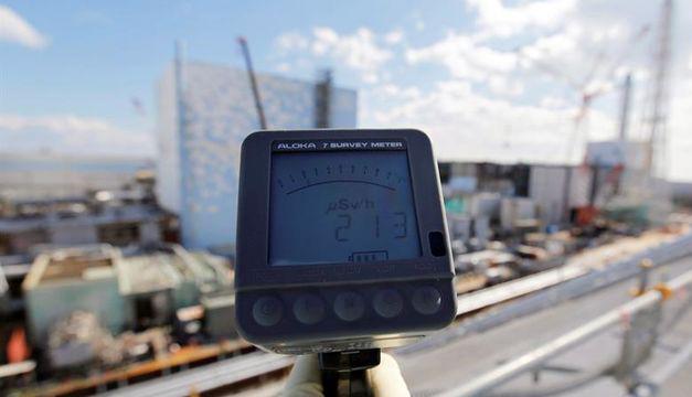 Un operario de TEPCO mide los niveles de radiación delante de los edificios de los reactores 2 y 3, que marca 213 microsievert, en la central nuclear de Fukushima Daiichi, en la localidad de Okuma, prefectura de Fukushima (Japón). EFE