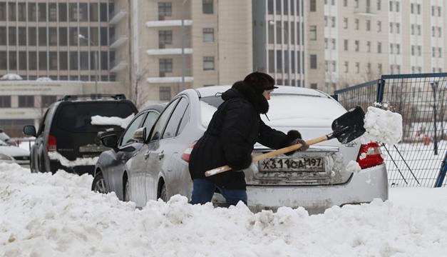na mujer usa una pala para retira la nieve que bloquea su coche. Agencia/EFE