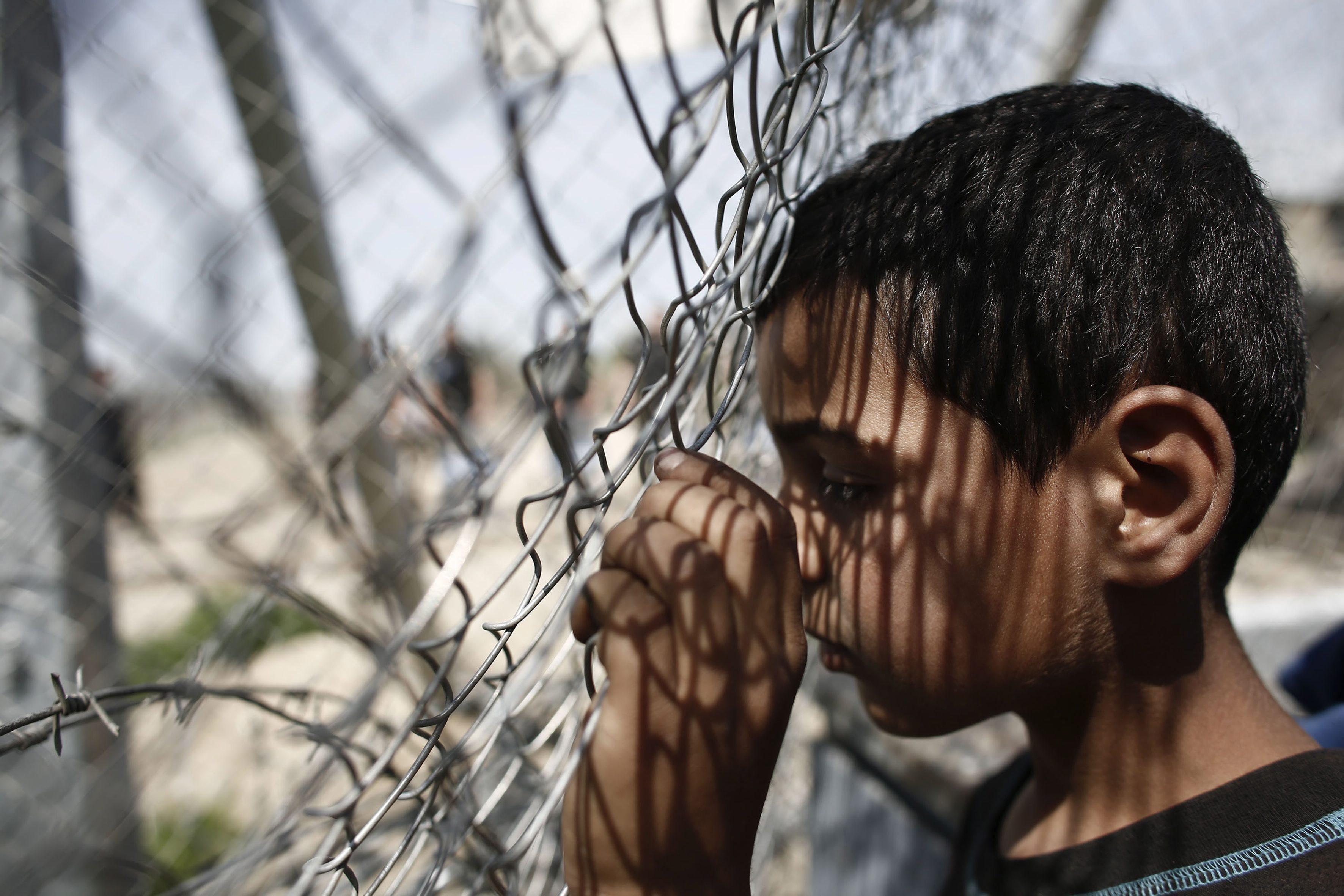 ATA02 IDOMENI (GRECIA), 07/04/2016.- Un niño se apoya en una valla durante una manifestación por la apertura de las fronteras a Macedonia en el campo improvisado de refugiados de Idomeni, Grecia hoy 7 de abril de 2016. Las llegadas de refugiados a las costas griegas desde Turquía se mantienen en niveles bajos, ya que en las últimas 24 horas han desembarcado 76 personas, la mayoría en la isla de Quíos. La tendencia se mantiene estable con respecto a las cifras de la víspera, cuando llegaron 68 refugiados a territorio griego. EFE/Kostas Tsironis