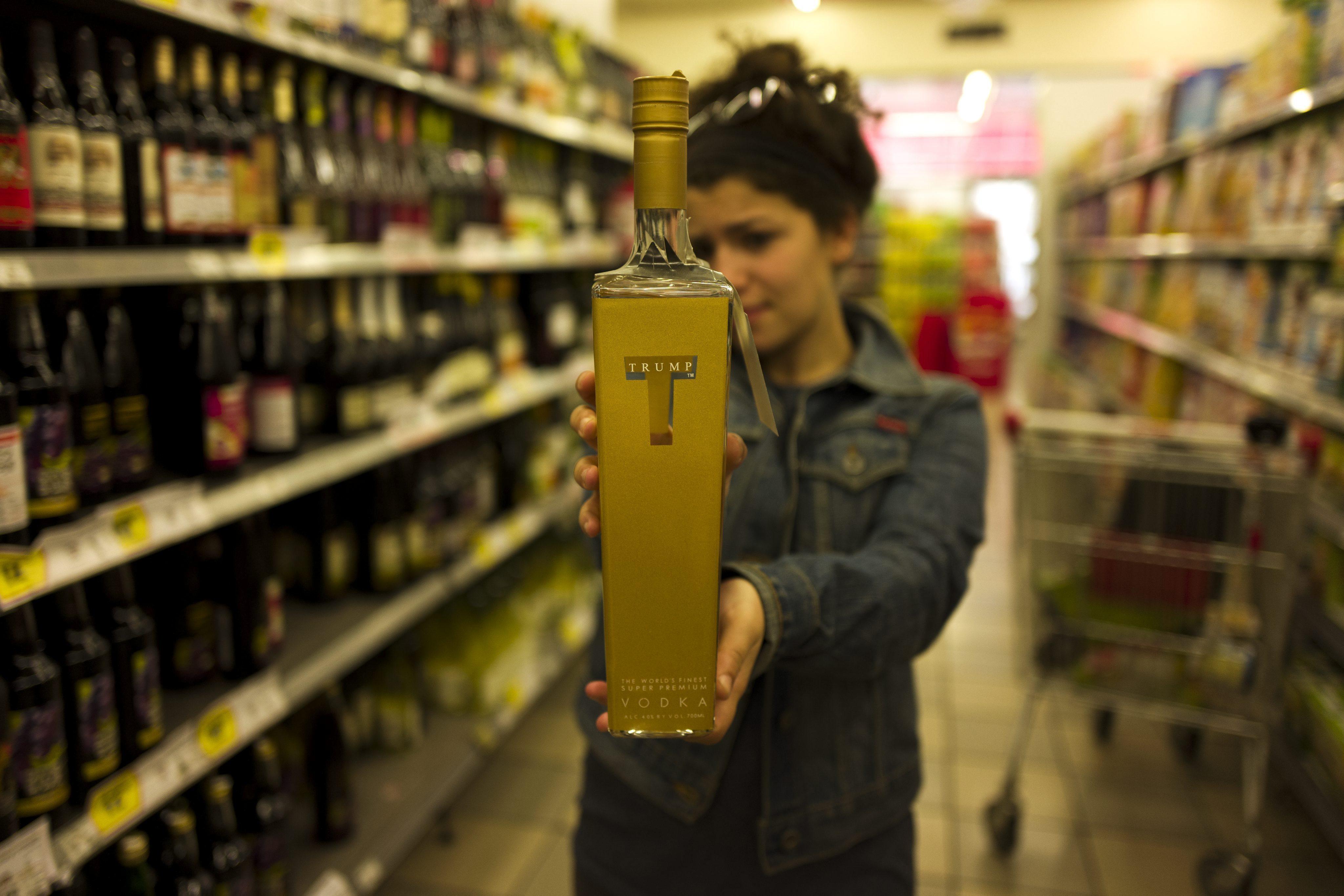 """JER01 JERUSALÉN (ISRAEL) 08/04/2016.- Una mujer muestra una botella de vodka de la marca Trump en un supermercado en Jerusalén (Israel) hoy, 8 de abril de 2016. Según medios israelíes, el vodka Trump, comercializado por las empresas de Donald Trump, aspirante republicano a la presidencia de Estados Unidos, ha sido publicitado como """"el mejor vodka del mundo"""" aunque tras 2013 algunas botellas no fueron consideradas aptas según los rituales Kosher. EFE/Jim Hollander"""