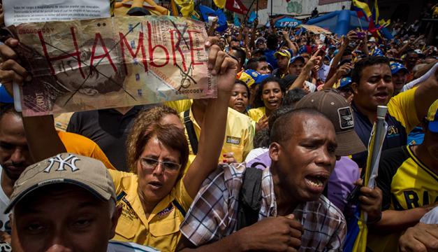 """Manifestante sostiene un letrero con la palabra """"Hambre"""" en una protesta contra el Gobierno venezolano. Foto: Agencia EFE"""
