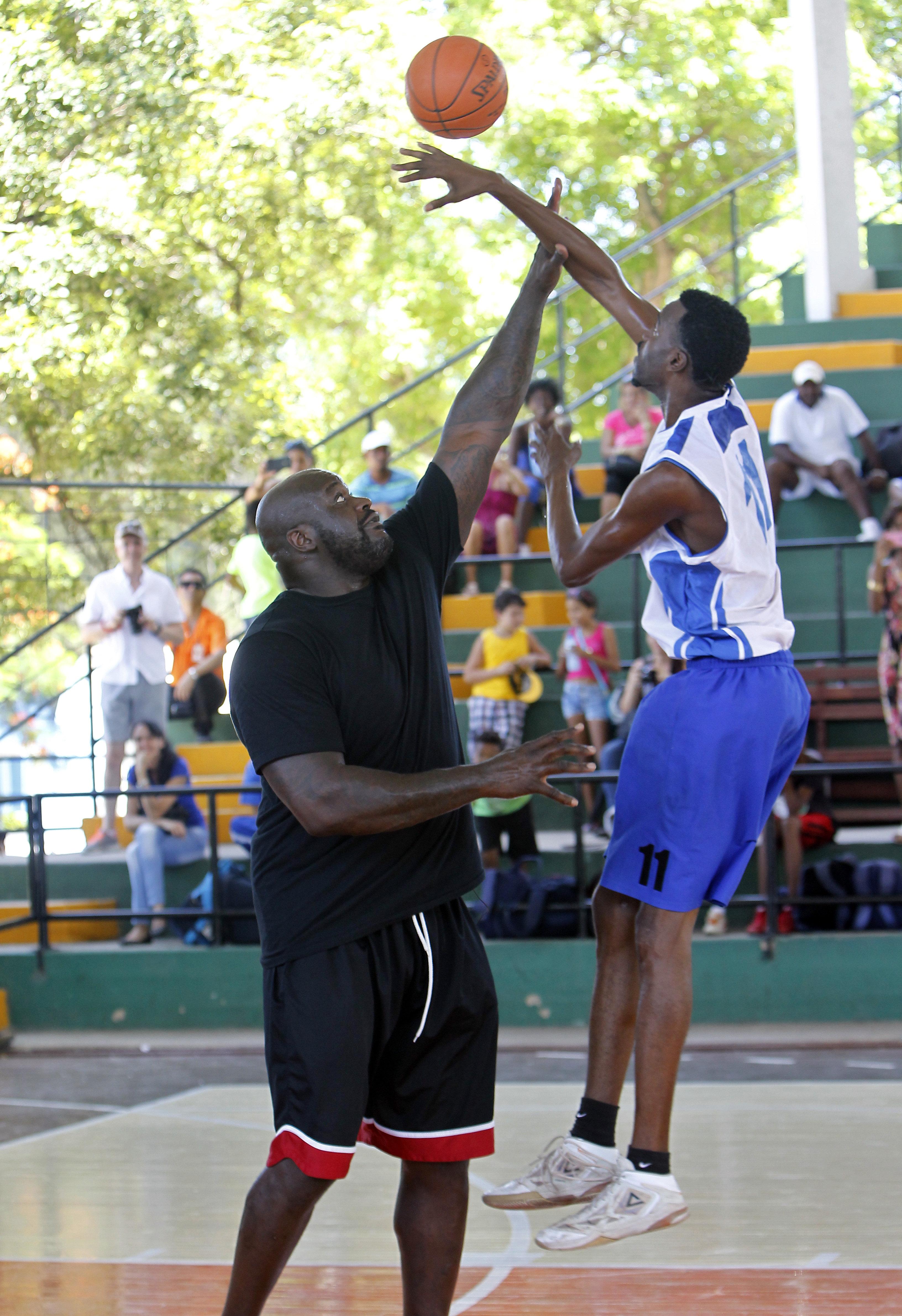 HAB102 LA HABANA (CUBA) 26/06/16.- La leyenda del baloncesto estadounidense Shaquille O'Neal (I) ofreció hoy, domingo 26 de junio de 2016, en una cancha de La Habana una clínica de su especialidad con un grupo de niños y jóvenes practicantes, como parte de un programa para promover la cooperación y el compromiso de EEUU con Cuba. O'Neal, quien jugó durante 19 temporadas en distintos equipos de la NBA, se encuentra en la isla como enviado del Departamento de Estado de EEUU, en el marco de la normalización de relaciones entre ambos países. EFE/Ernesto Mastrascusa
