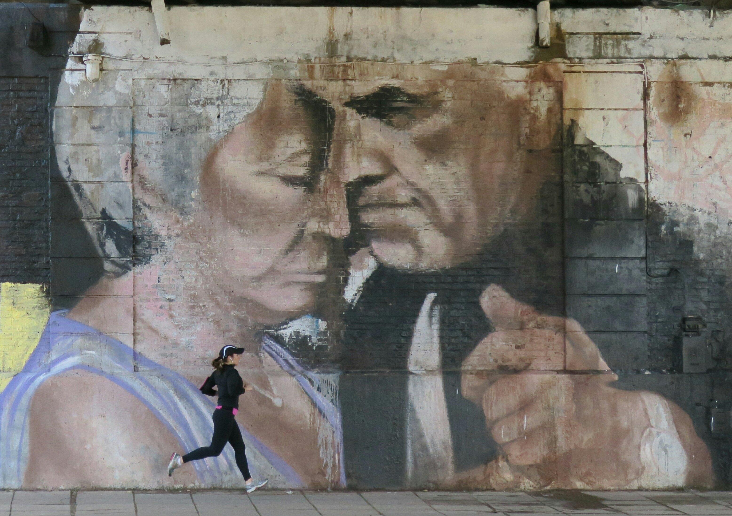 BAS01. BUENOS AIRES (ARGENTINA), 31/07/2016.- Fotografía del 28 de julio de 2016, de una mujer corriendo junto a un fragmento del mural pintado por el artista argentino Alfredo Segatori, en Buenos Aires (Argentina). El bandoneón, la tradicional milonga, Carlos Gardel, la pasión en el tango y su vínculo con las carreras de caballos componen un mural que ha trasladado el ritmo del 2x4 hasta las mismas paredes de Buenos Aires. Un homenaje producto de los aerosoles del artista argentino Alfredo Segatori. EFE/Irene Valiente