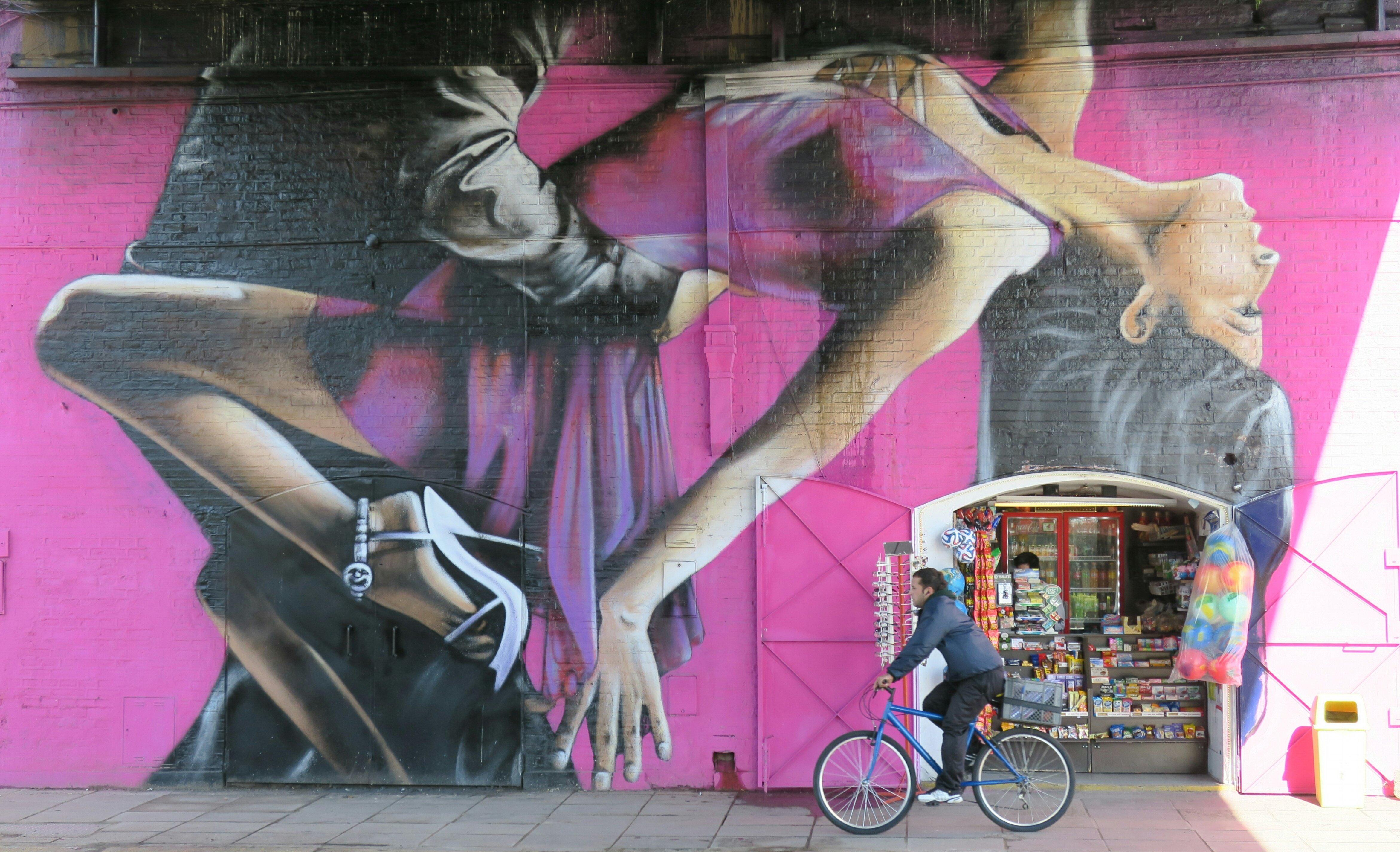 BAS01. BUENOS AIRES (ARGENTINA), 31/07/2016.- Fotografía del 28 de julio de 2016, de una persona pasando en bicicleta junto a un fragmento del mural pintado por el artista argentino Alfredo Segatori, en Buenos Aires (Argentina). El bandoneón, la tradicional milonga, Carlos Gardel, la pasión en el tango y su vínculo con las carreras de caballos componen un mural que ha trasladado el ritmo del 2x4 hasta las mismas paredes de Buenos Aires. Un homenaje producto de los aerosoles del artista argentino Alfredo Segatori. EFE/Irene Valiente