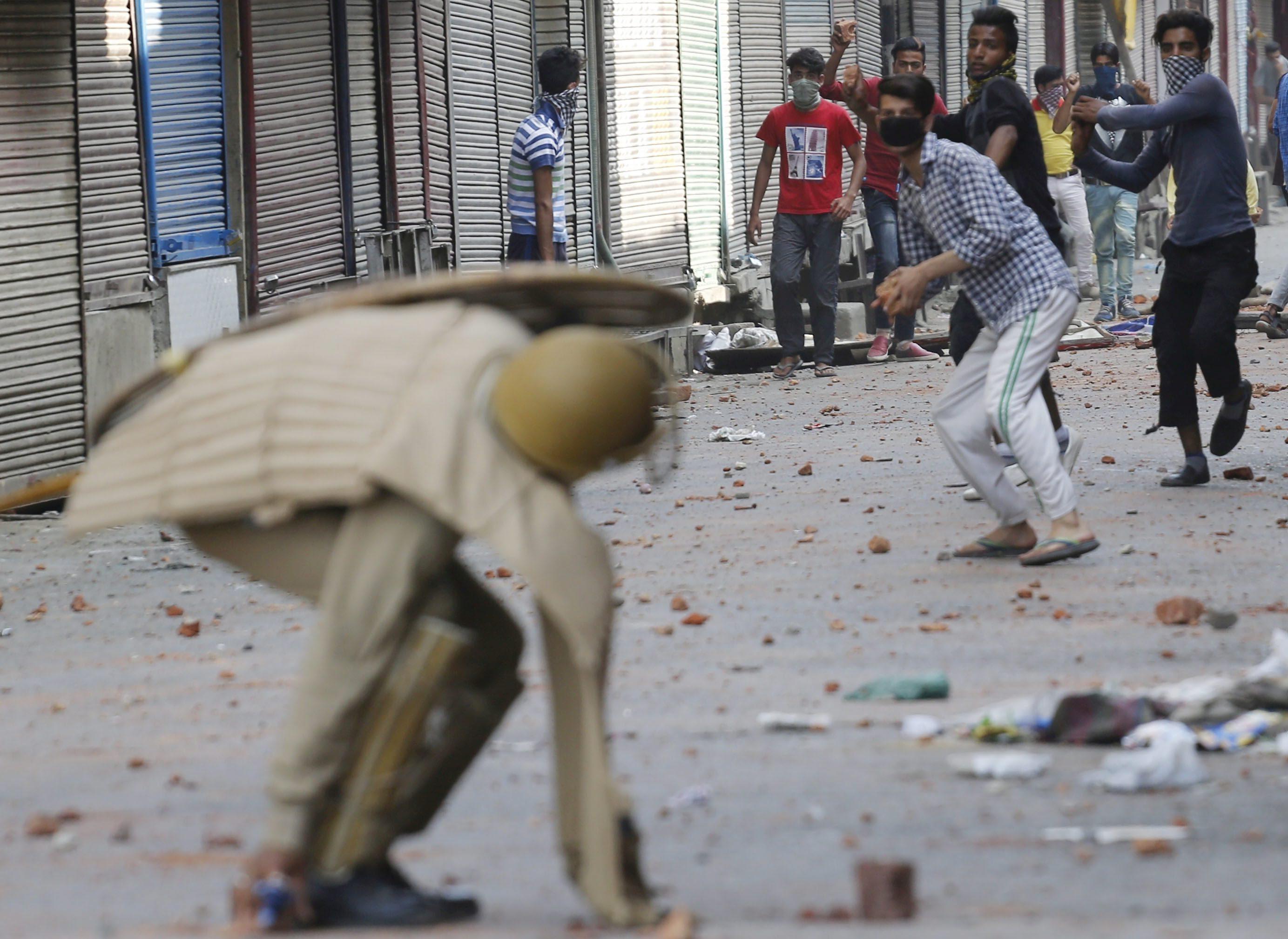 FAR02 SRINAGAR (INDIA) 11/07/2016.- Un grupo de manifestantes lanza piedras a un miembro de la policía durante una protesta violenta en Srinagar, la capital de verano de Cachemira, India hoy, 11 de julio de 2016. El número de muertos en protestas violentas en la Cachemira india se elevó ayer a 21 y el de heridos a cerca de 200, en el segundo día de disturbios en la región por la fallecimiento el viernes de un terrorista del grupo separatista Hizb-ul-Mujahideen (HM) a manos de las fuerzas de seguridad. En Srinagar hay calles, desiertas, cortadas con alambres de espino en las que montan guardia efectivos de las fuerzas de seguridad indias armados con fusiles. EFE/Farooq Khan