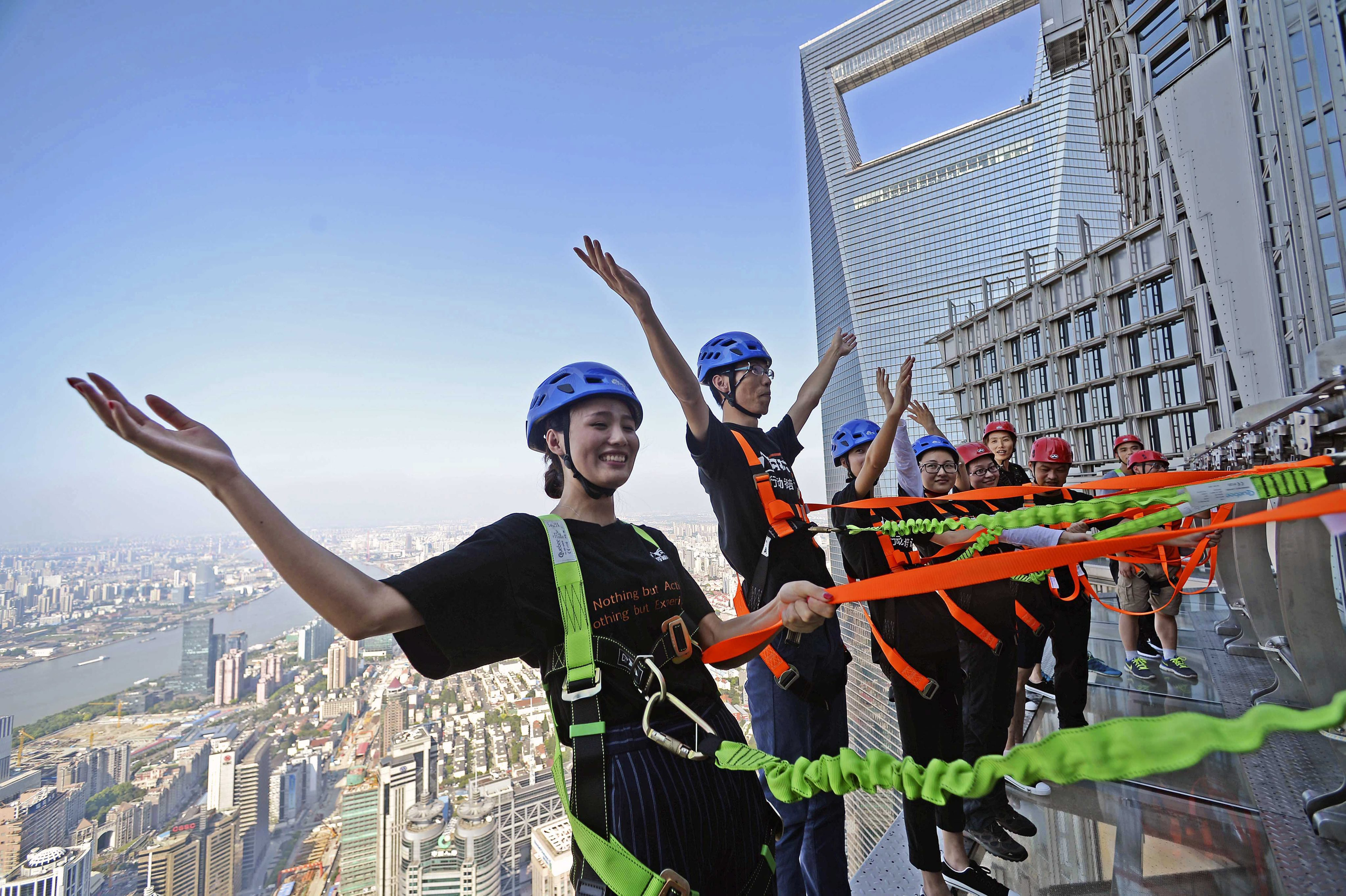 CH01. SHANGHÁI (CHINA), 28/07/2016.- Fotografía disponible hoy, viernes 29 de julio de 2016, de personas caminando sobre una pasarela acristalada en el piso 88 de la Torre Jinmao en Shanghái (China). La pasarela está abierta a los turistas, quienes pueden caminar ayudados de cuerdas de seguridad. EFE/XI LI/PROHIBIDO SU USO EN CHINA