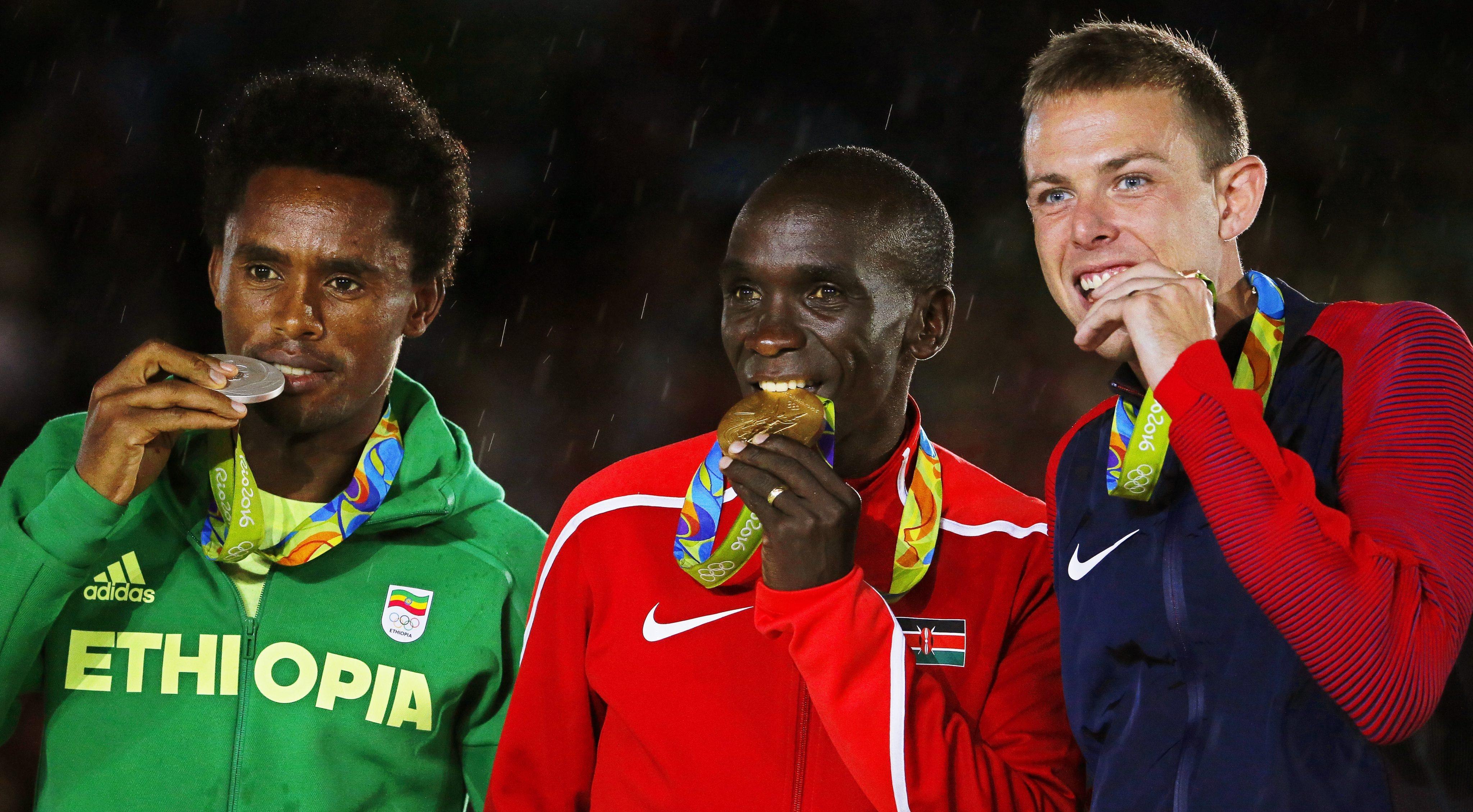 . Rio De Janeiro (Brazil), 21/08/2016.- Eliud Kipchoge (C) of Kenya poses with his gold medal on the podium after winning the men's Marathon race of the Rio 2016 Olympic Games Athletics, Track and Field events at the Sambodromo in Rio de Janeiro, Brazil, 21 August 2016. Kipchoge won ahead of second placed Feyisa Lilesa (L) of Ethiopia and third placed Galen Rupp (R) of the USA. (Atletismo, Etiopía, Brasil, Kenia, Estados Unidos) EFE/EPA/SERGEI ILNITSKY