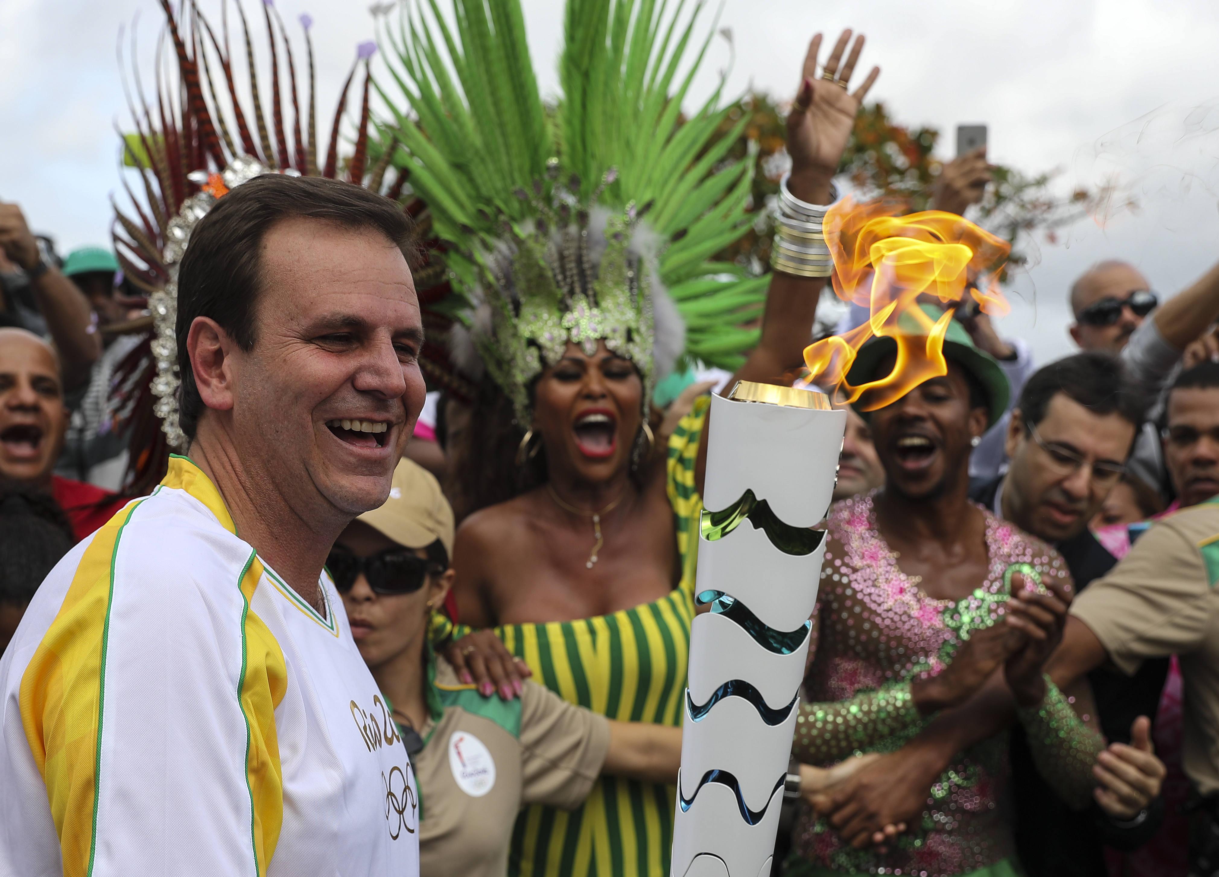BRA01. RÍO DE JANEIRO (BRASIL), 03/08/16.- El alcalde de Río de Janeiro, Eduardo Paes (i), recibe la antorcha olímpica hoy, miércoles 3 de agosto de 2016, a su llegada en la ciudad de Río de Janeiro (Brasil), sede de los Juegos Olímpicos que empiezan el viernes 5 de agosto. EFE/ Antonio Lacerda