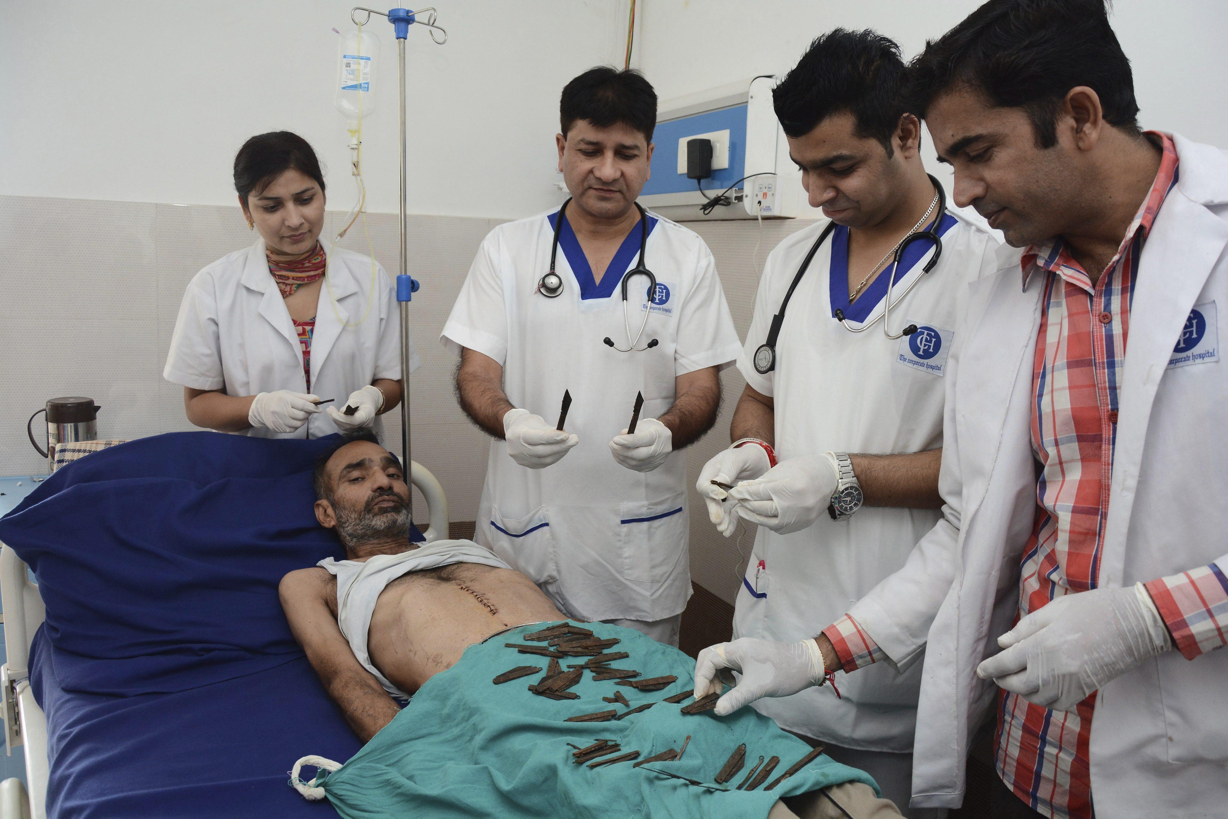 IN01 AMRITSAR (INDIA) 23/08/2016.- El Dr. Jatinder Malhorta (3i) y miembros de su equipo muestran los 40 navajas recuperadas del estómago de su paciente Surjeet Singh (tumbado en la cama) tras ser operado en el hospital Corporate en Amritsar (India) hoy, 23 de agosto de 2016. Surjeet Singh sufre de un trastorno psiquiátrico por el que ha ingerido 40 navajas en los últimos dos meses. EFE/Raminder Pal Singh