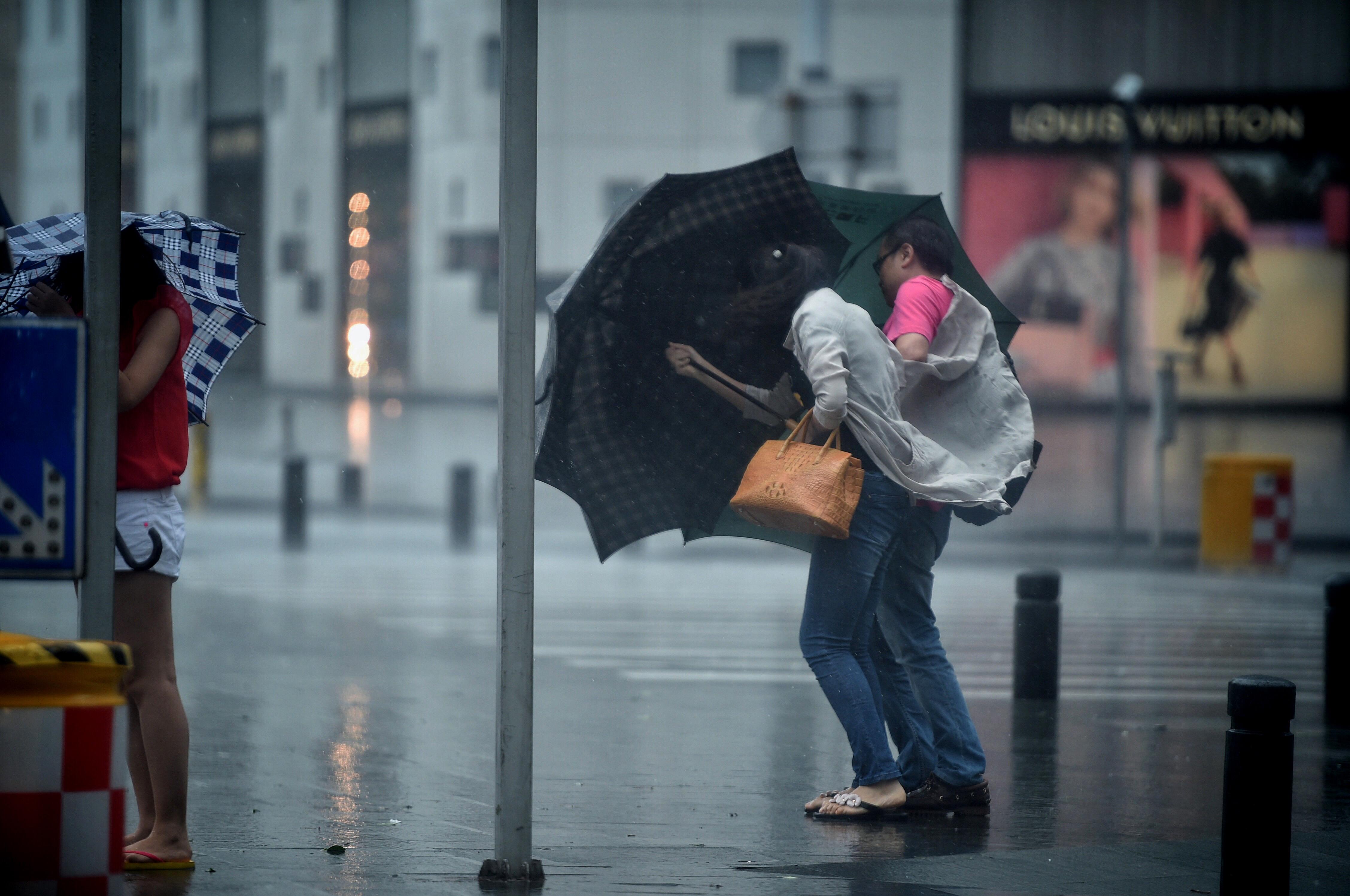 (160802) -- GUANGDONG, agosto 2, 2016 (Xinhua) -- Peatones intentan cruzar una calle a pesar del fuerte viento en Shenzhen, en la provincia de Guangdong, en el sur de China, el 2 de agosto de 2016. El tifón Nida tocó tierra a las 3:35 horas del martes en la península Dapeng de la ciudad de Shenzhen, en la provincia de Guangdong, en el sur de China, informaron las autoridades meteorológicas locales. El fuerte tifón, con vientos de hasta 151.2 kilómetros por hora, se está desplazando hacia el noroeste con una velocidad de 25 kilómetros por hora, y está previsto que azote las ciudades de Shenzhen, Dongguan, Guangzhou, Foshan y Zhaoqing, así como la vecina región autónoma de la etnia zhuang de Guangxi, según las autoridades meteorológicas provinciales de Guangdong. (Xinhua/Mao Siqian) (ah)