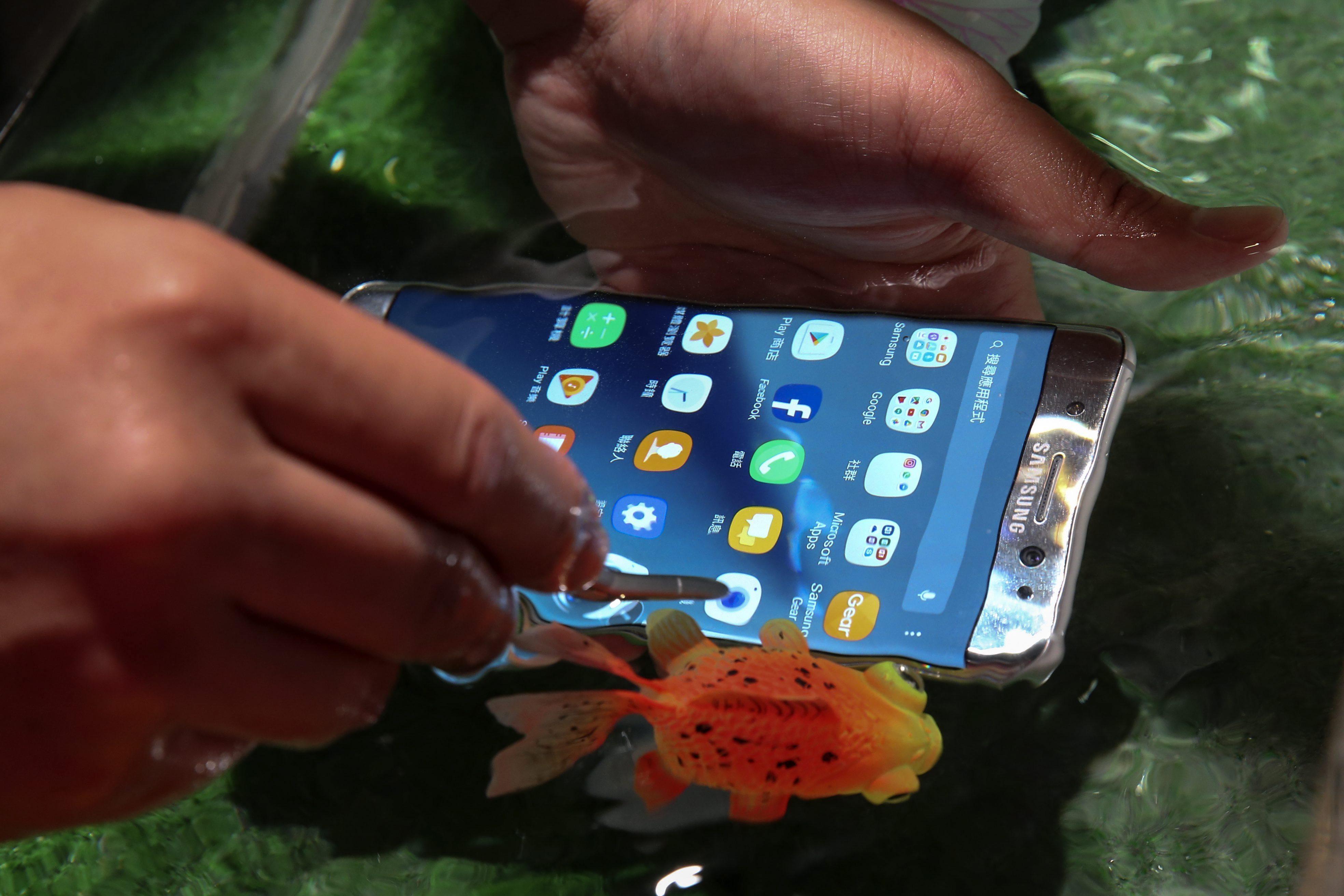 """RIT06 TAIPEI (TAIWÁN) 05/08/2016.- Un usuario prueba un Galaxy Note 7, la última versión de """"phablet"""" o tabléfono de la compañía Samsung Electronics, mientras lo sumerge en el agua, en Taipei, Taiwán, hoy, 5 de agosto de 2016. El tabléfono, con una función de reconocimiento de iris que ha suscitado gran interés en el mercado, estará disponible mediante encargo a partir de mañana. EFE/Ritchie B. Tongo"""