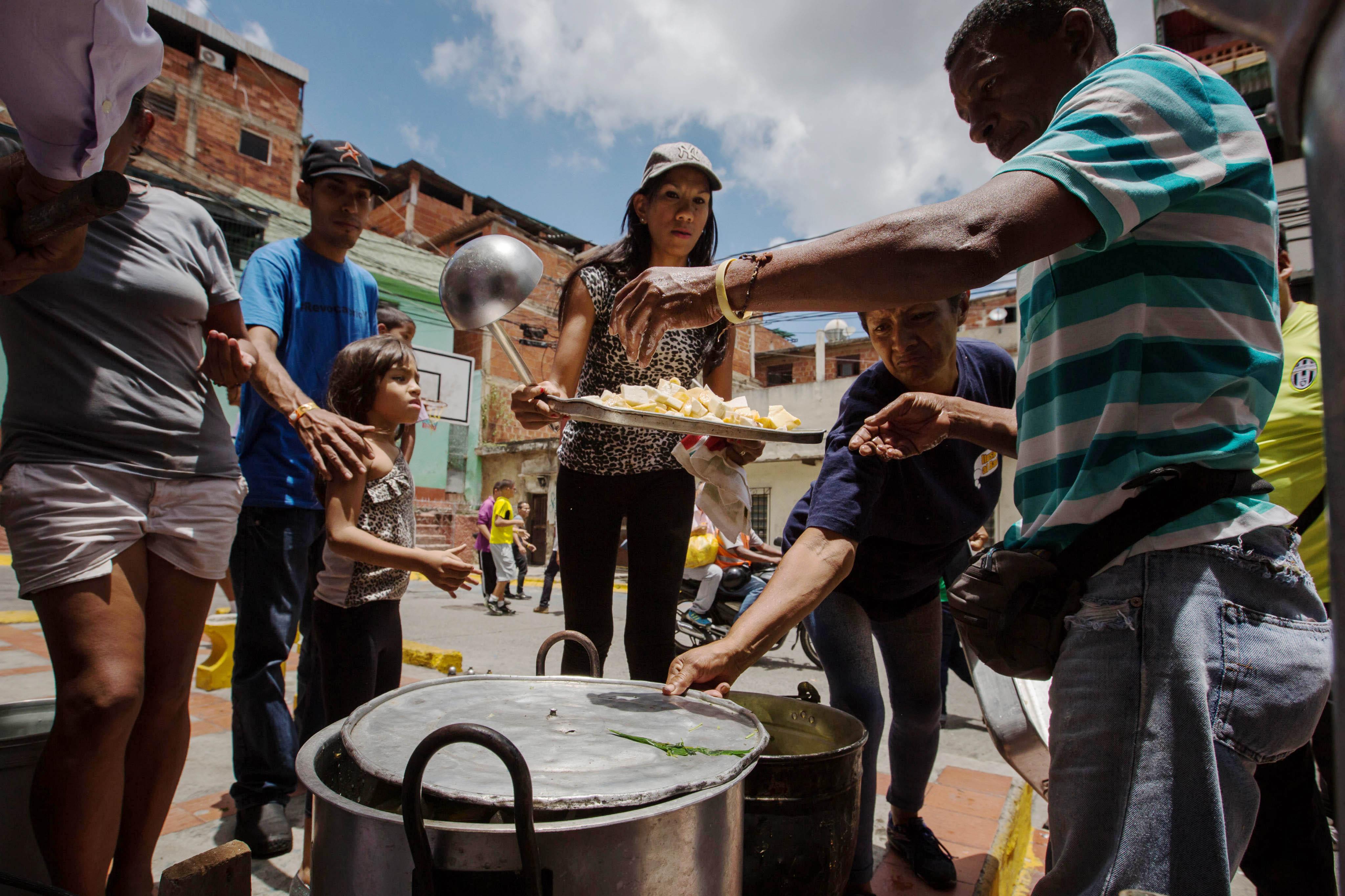 """CAR01. CARACAS (VENEZUELA), 10/09/2016.- Un grupo de personas preparan un sancocho hoy, s·bado 10 de septiembre del 2016, en la ciudad de Caracas (Venezuela). En el barrio la UniÛn, ubicado en la favela m·s grande de AmÈrica Latina asentada en el este de Caracas, se preparÛ hoy un gran """"sancocho"""" como se le conoce en Venezuela a la sopa cocinada con varios tipos de verduras y carnes, para alimentar a los vecinos, muchos de ellos con varios dÌas de hambre. EFE/MIGUEL GUTI…RREZ"""