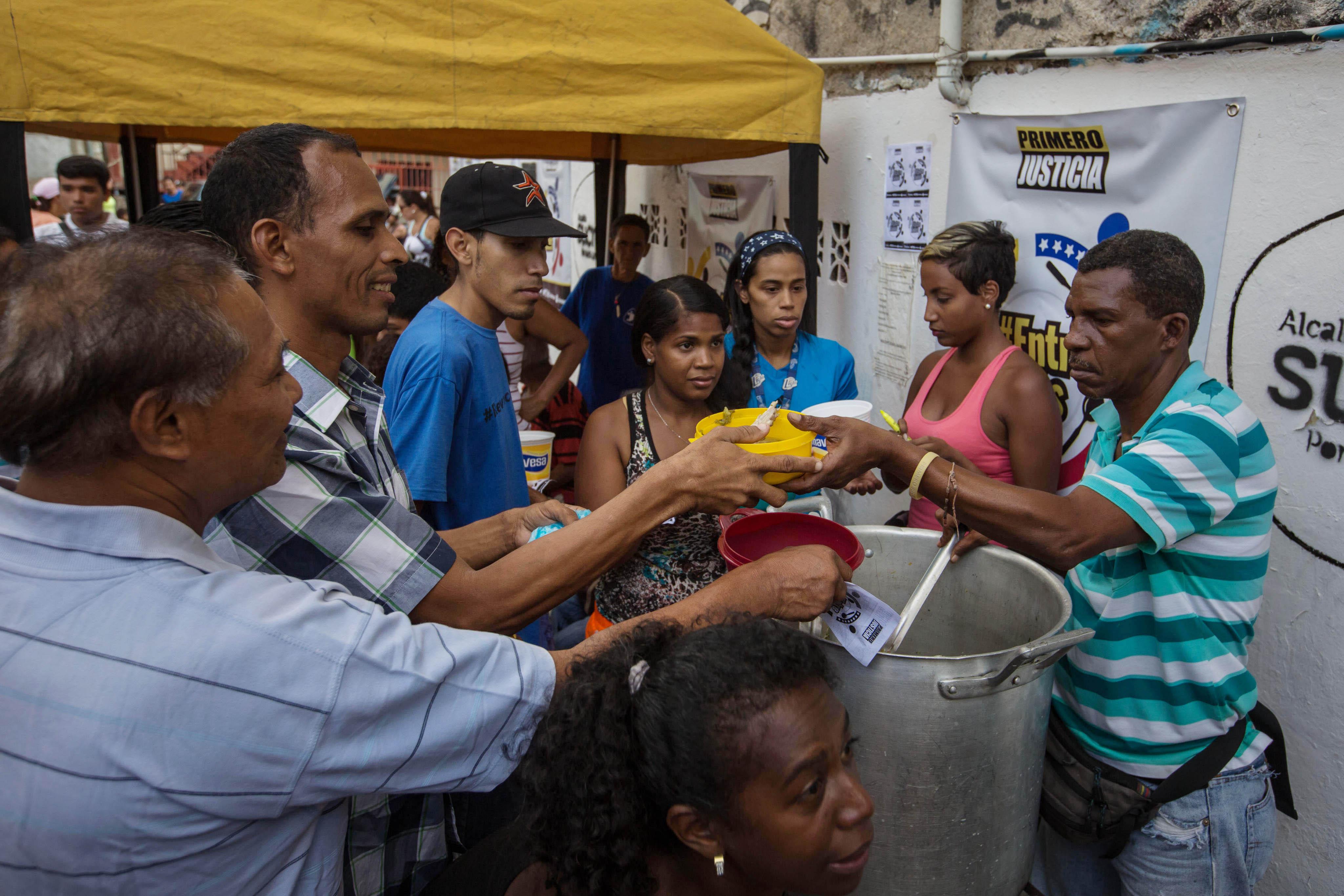"""CAR08. CARACAS (VENEZUELA), 10/09/2016.- Habitantes comen de un sancocho comunal hoy, s·bado 10 de septiembre del 2016, en la ciudad de Caracas (Venezuela). En el barrio la UniÛn, ubicado en la favela m·s grande de AmÈrica Latina asentada en el este de Caracas, se preparÛ hoy un gran """"sancocho"""" como se le conoce en Venezuela a la sopa cocinada con varios tipos de verduras y carnes, para alimentar a los vecinos, muchos de ellos con varios dÌas de hambre. EFE/MIGUEL GUTI…RREZ"""