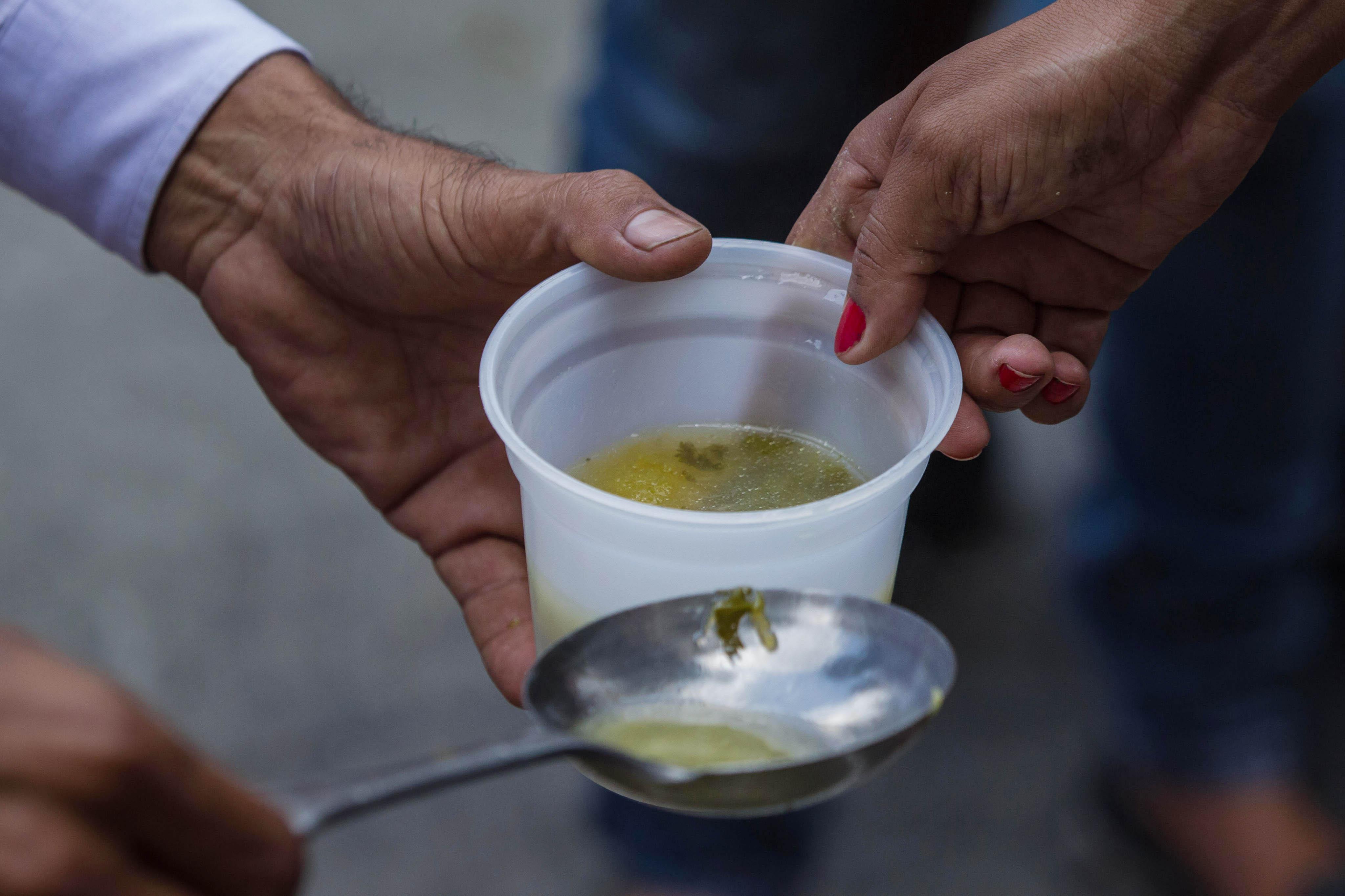"""CAR06. CARACAS (VENEZUELA), 10/09/2016.- Un grupo de personas preparan un sancocho hoy, s·bado 10 de septiembre del 2016, en la ciudad de Caracas (Venezuela). En el barrio la UniÛn, ubicado en la favela m·s grande de AmÈrica Latina asentada en el este de Caracas, se preparÛ hoy un gran """"sancocho"""" como se le conoce en Venezuela a la sopa cocinada con varios tipos de verduras y carnes, para alimentar a los vecinos, muchos de ellos con varios dÌas de hambre. EFE/MIGUEL GUTI…RREZ"""