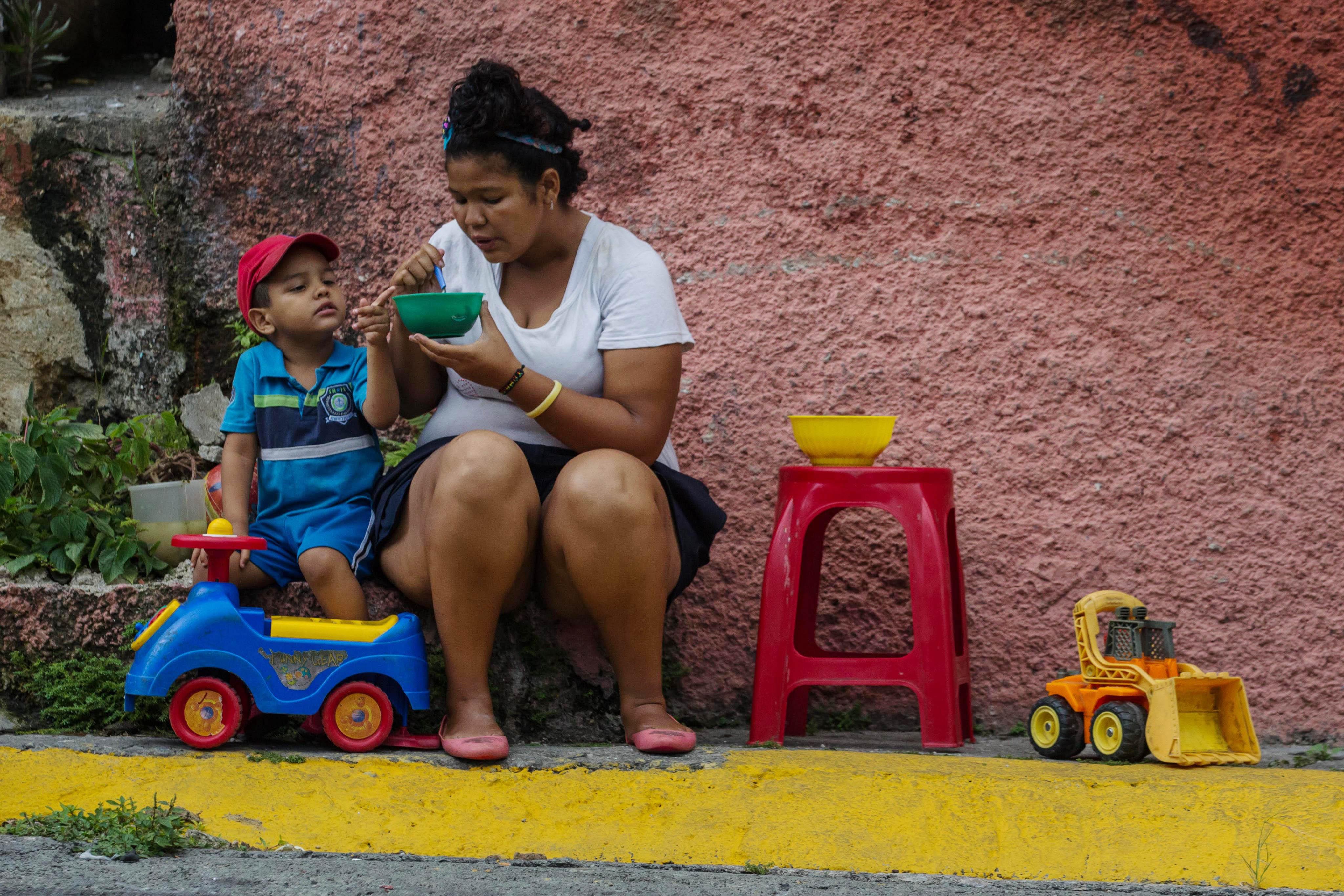 """CAR07. CARACAS (VENEZUELA), 10/09/2016.- Habitantes comen de un sancocho comunal hoy, s·bado 10 de septiembre del 2016, en la ciudad de Caracas (Venezuela). En el barrio la UniÛn, ubicado en la favela m·s grande de AmÈrica Latina asentada en el este de Caracas, se preparÛ hoy un gran """"sancocho"""" como se le conoce en Venezuela a la sopa cocinada con varios tipos de verduras y carnes, para alimentar a los vecinos, muchos de ellos con varios dÌas de hambre. EFE/MIGUEL GUTI…RREZ"""