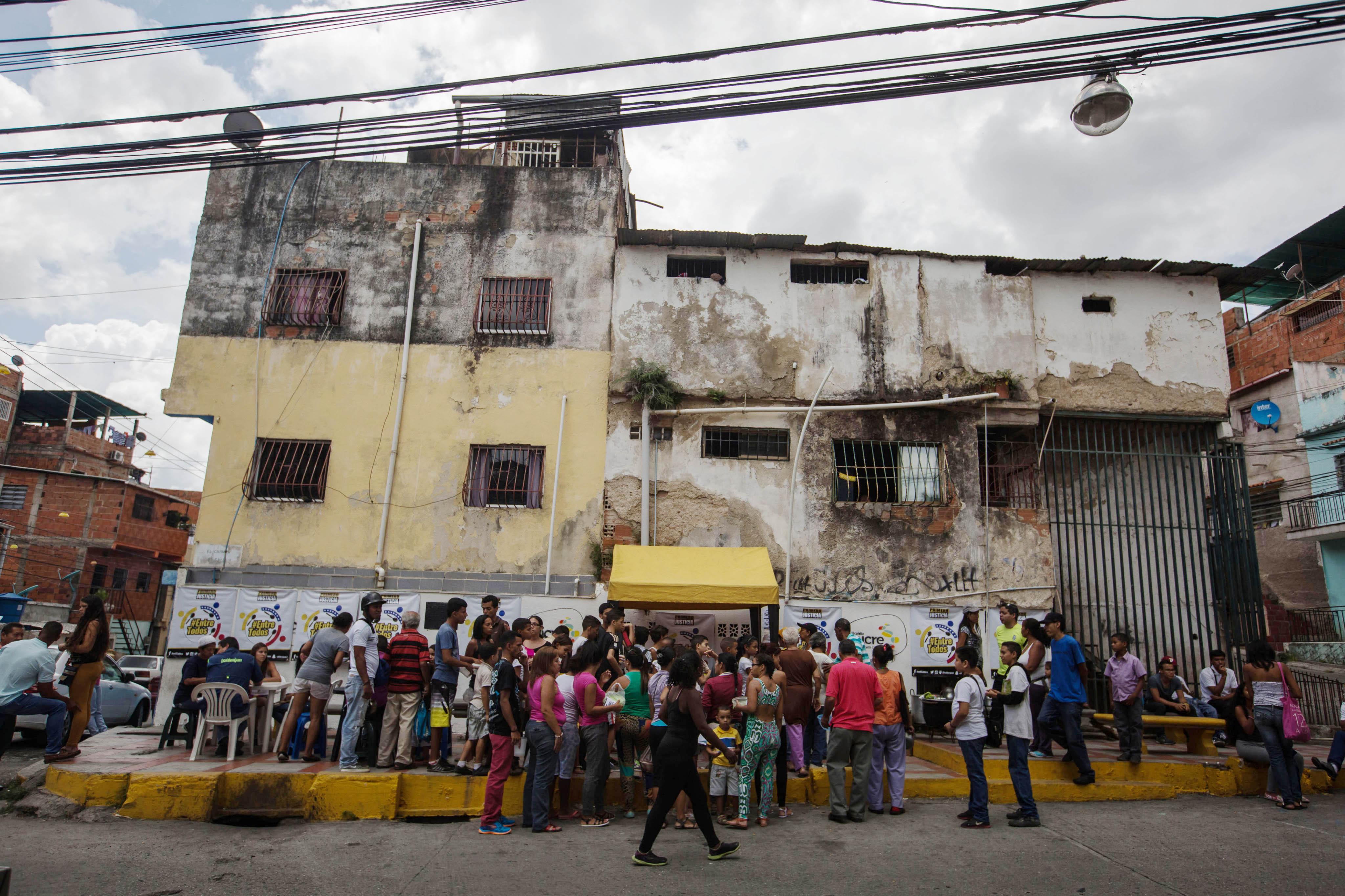 """CAR03. CARACAS (VENEZUELA), 10/09/2016.- Un grupo de personas preparan un sancocho hoy, s·bado 10 de septiembre del 2016, en la ciudad de Caracas (Venezuela). En el barrio la UniÛn, ubicado en la favela m·s grande de AmÈrica Latina asentada en el este de Caracas, se preparÛ hoy un gran """"sancocho"""" como se le conoce en Venezuela a la sopa cocinada con varios tipos de verduras y carnes, para alimentar a los vecinos, muchos de ellos con varios dÌas de hambre. EFE/MIGUEL GUTI…RREZ"""