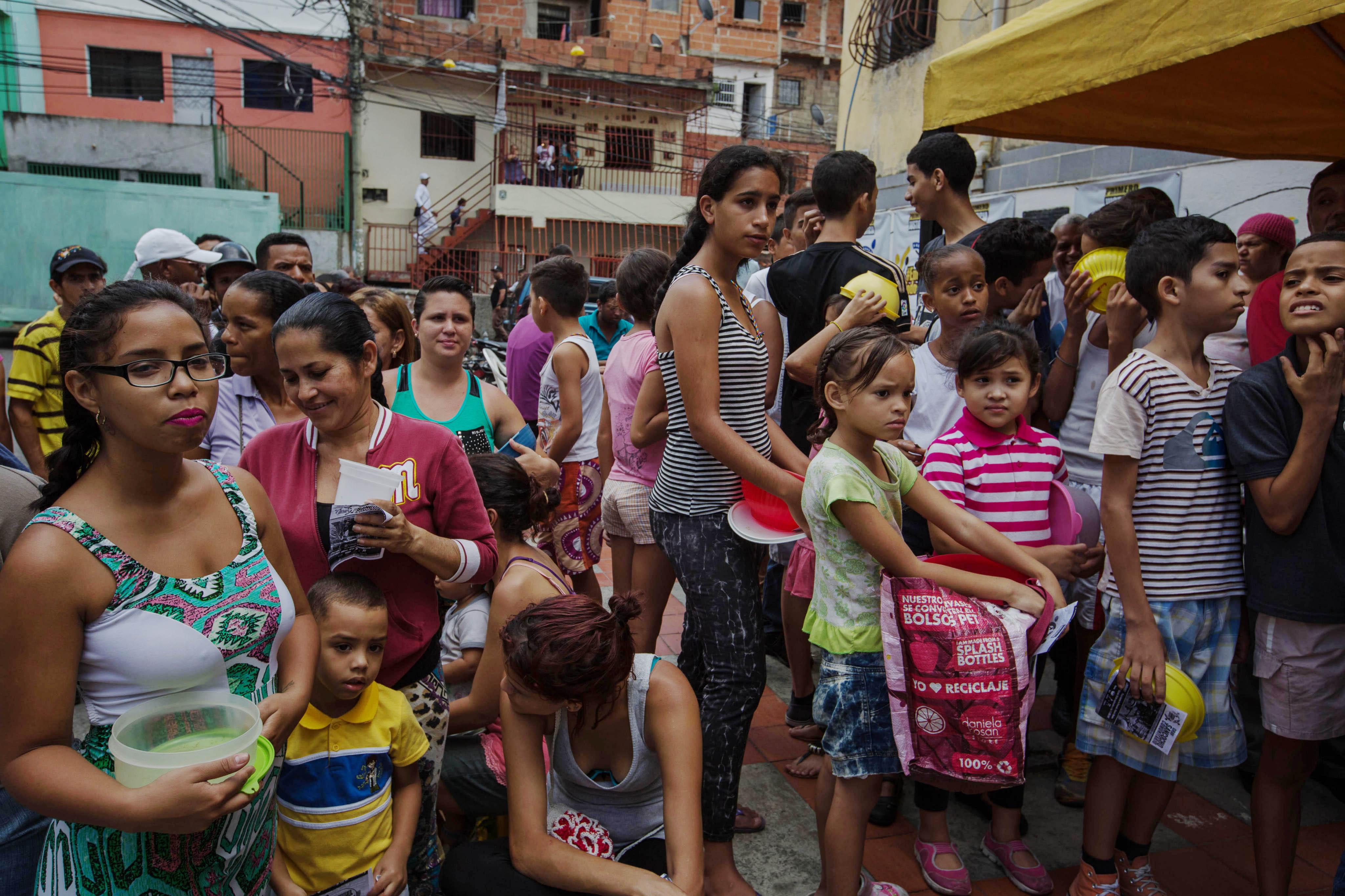 """CAR04. CARACAS (VENEZUELA), 10/09/2016.- Habitantes esperan para recibir porciones de un sancocho hoy, s·bado 10 de septiembre del 2016, en la ciudad de Caracas (Venezuela). En el barrio la UniÛn, ubicado en la favela m·s grande de AmÈrica Latina asentada en el este de Caracas, se preparÛ hoy un gran """"sancocho"""" como se le conoce en Venezuela a la sopa cocinada con varios tipos de verduras y carnes, para alimentar a los vecinos, muchos de ellos con varios dÌas de hambre. EFE/MIGUEL GUTI…RREZ"""