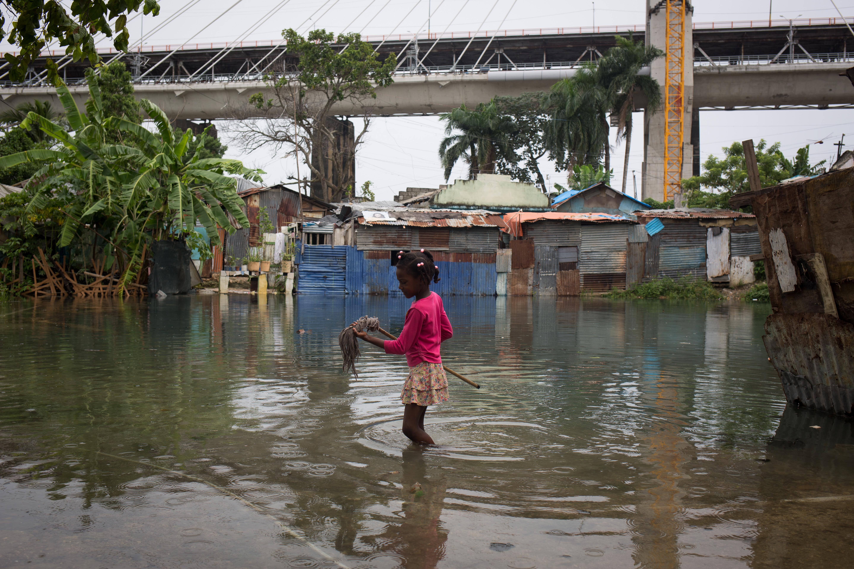 """(161006) -- SANTO DOMINGO, octubre 6, 2016 (Xinhua) -- Imagen cedida por el Fondo de Naciones Unidas para la Infancia (UNICEF, por sus siglas en inglés) del 4 de octubre de 2016 de una niña caminando por el agua de la inundación tras el paso del huracán """"Matthew"""", en el barrio de Los Guandules, en Santo Domingo, capital de República Dominicana. Al menos cuatro muertos, entre ellos tres niños, y unas 35,000 familias desplazadas es el saldo preliminar por el paso del huracán """"Matthew"""" en República Dominicana, de acuerdo con el Centro de Operaciones de Emergencias (COE). El COE, principal organismo de asistencia y protección civil, agregó que más de 3,000 viviendas resultaron afectadas y 1,500 personas fueron evacuadas a albergues oficiales, además de que numerosas comunidades quedaron aisladas. (Xinhua/UNICEF) (jg) (ce) ***CREDITO OBLIGATORIO*** ***NO ARCHIVO-NO VENTAS*** ***SOLO USO EDITORIAL***"""