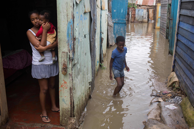 """(161006) -- SANTO DOMINGO, octubre 6, 2016 (Xinhua) -- Imagen cedida por el Fondo de Naciones Unidas para la Infancia (UNICEF, por sus siglas en inglés) del 4 de octubre de 2016 de una mujer y sus hijos observando la inundación tras el paso del huracán """"Matthew"""", en el barrio de Los Guandules, en Santo Domingo, capital de República Dominicana. Al menos cuatro muertos, entre ellos tres niños, y unas 35,000 familias desplazadas es el saldo preliminar por el paso del huracán """"Matthew"""" en República Dominicana, de acuerdo con el Centro de Operaciones de Emergencias (COE). El COE, principal organismo de asistencia y protección civil, agregó que más de 3,000 viviendas resultaron afectadas y 1,500 personas fueron evacuadas a albergues oficiales, además de que numerosas comunidades quedaron aisladas. (Xinhua/UNICEF) (jg) (ce) ***CREDITO OBLIGATORIO*** ***NO ARCHIVO-NO VENTAS*** ***SOLO USO EDITORIAL***"""
