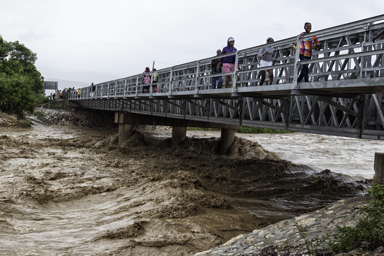 """(161006) -- PUERTO PRINCIPE, octubre 6, 2016 (Xinhua) -- Imagen cedida por el Fondo de Naciones Unidas para la Infancia (UNICEF, por sus siglas en inglés) del 4 de octubre de 2016 de personas cruzando un puente sobre el río Grise, durante el primer día del paso del huracán """"Matthew"""", en la cidad de Puerto Príncipe, capital de Haití. El huracán """"Matthew"""" de categoría 4, afectó el martes Haití desplazándose con vientos de hasta 320km por hora, destruyendo viviendas y caminos y arrancando árboles. El huracán """"Matthew"""" ha dejado al menos 108 muertos en Haití, informó el jueves el ministro haitiano de Interior, Francois Anick Joseph. (Xinhua/UNICEF) (jg) (ce) ***CREDITO OBLIGATORIO*** ***NO ARCHIVO-NO VENTAS*** ***SOLO USO EDITORIAL***"""