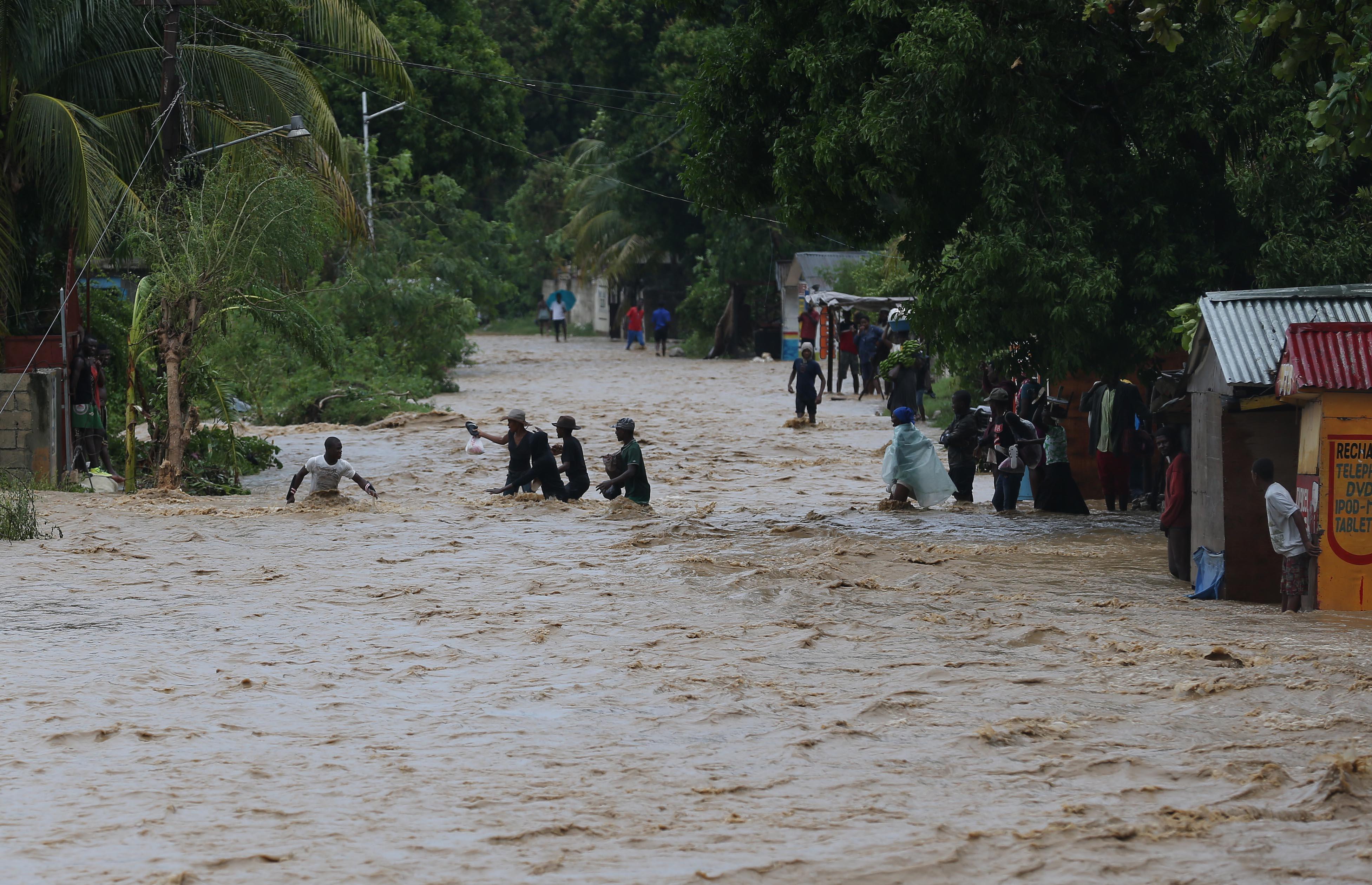 HAI01. LEOGANE (HAITI), 05/10/16.- Personas intentan cruzar una calle inundada tras el paso del huracán Matthew hoy, 5 de octubre de 2016, en Leogane (Haití). El poderoso huracán de categoría 4 Matthew continúa su ruta con vientos máximos de 140 millas por hora (220 km/h). La región sur de Haití sigue hoy incomunicada por los estragos causados por el poderoso huracán Matthew, que azotó el país este martes y causó al menos nueve muertos. EFE/Orlando Barría