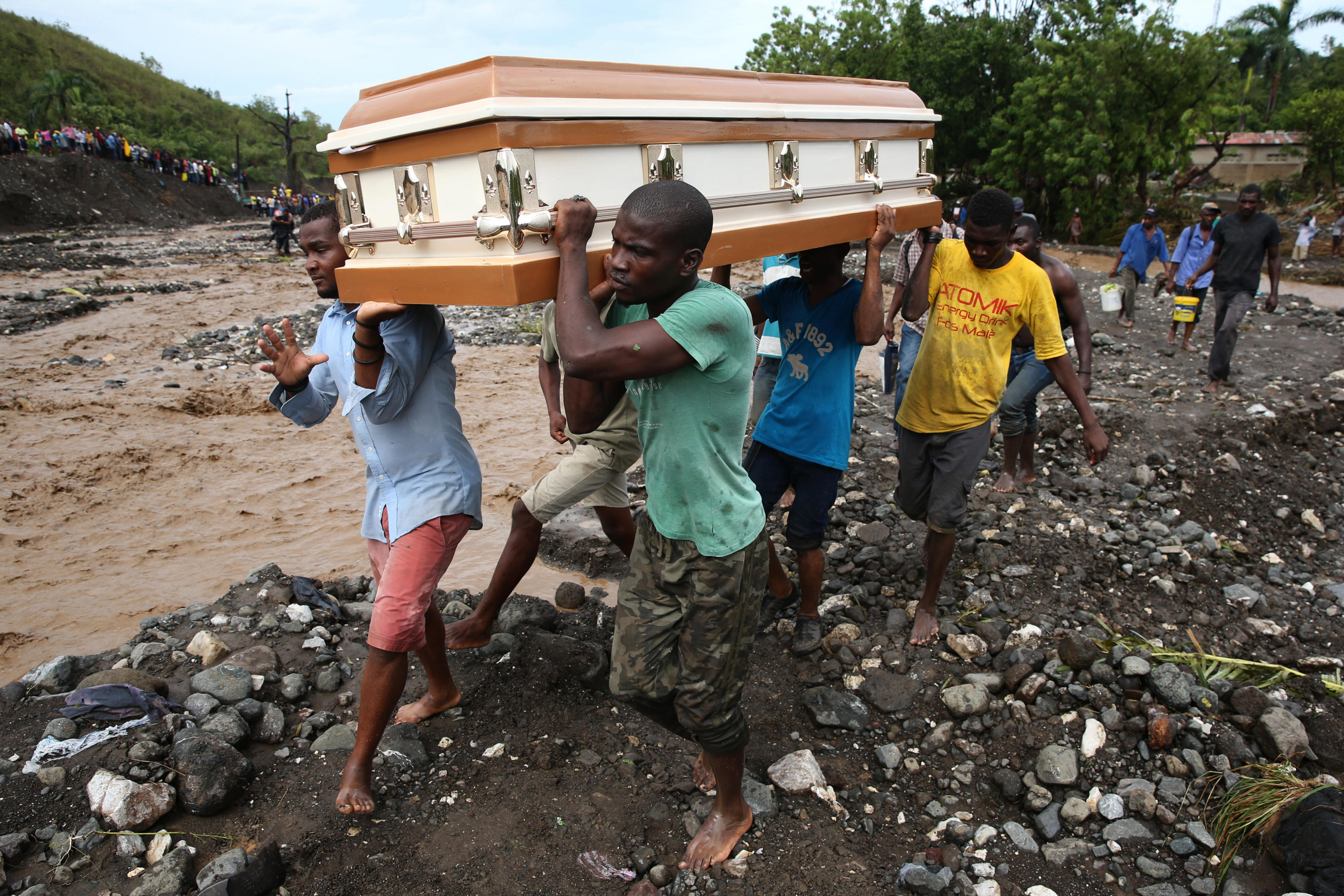 HAI01. PETIT GOAVE (HAITI), 05/10/16.- Varios hombres cargan un ataúd e intentan cruzar el río La Digue, debido al derrumbe del único puente que conecta con el sur, tras el paso del huracán Matthew hoy, 5 de octubre de 2016, en Petit Goave (Haití). El impacto del huracán Matthew en Haití, donde dejó al menos nueve muertos, miles de desplazados y comunidades incomunicadas, principalmente en el suroeste, obligó hoy a las autoridades electorales a aplazar los comicios del domingo. EFE/Orlando Barría